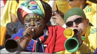 Football fans blowing vuvuzelas