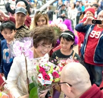 圖為接機弟子向師母獻花