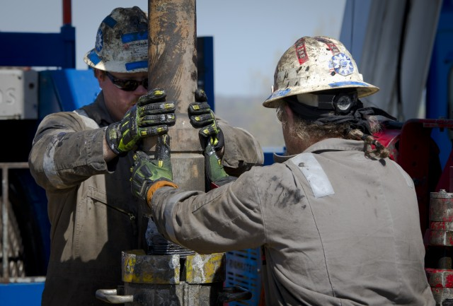 Workers change the pipes in a fracking operation. (Mladen Antonov/AFP/Getty Images)