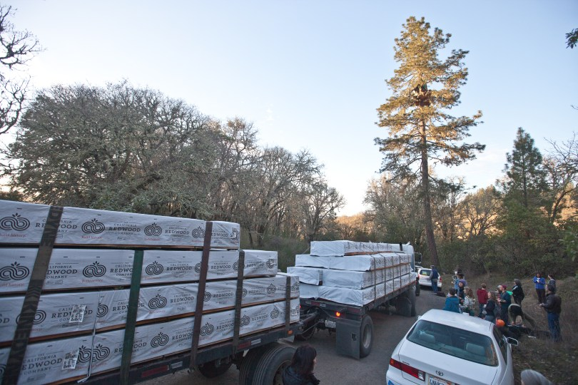 A big-rig piled with wood for a fence around the construction site arrived on Feb. 28. (Deborah Svoboda/KQED)