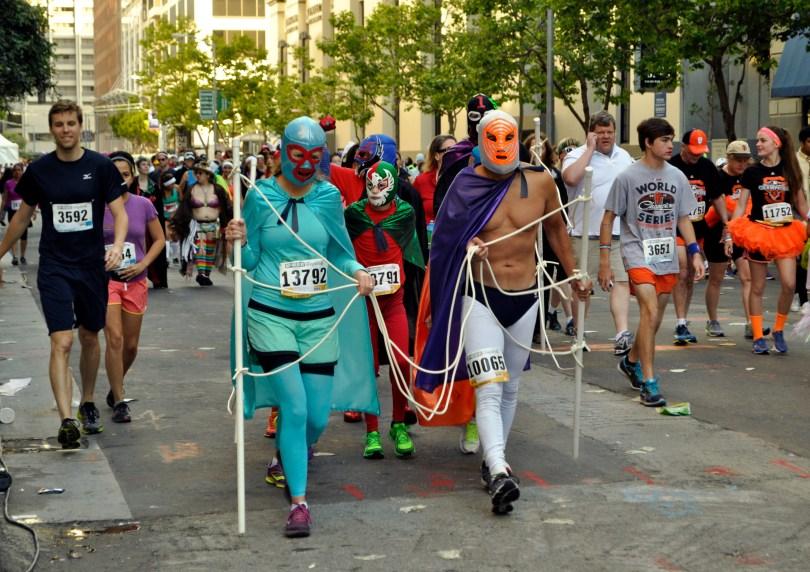 Runners dressed in lucha libre costumes (Lauren Benichou/KQED)