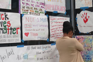 Monday, before more protests erupted Monday night, an Oakland resident read signs that had been taped to windows of downtown businesses. Some businesses had their windows broken earlier this weekend and covered the broken glass with signs protesting the Zimmerman decision.