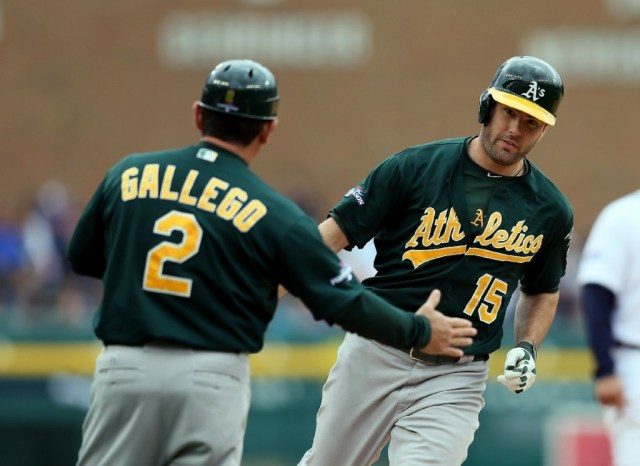 Oakland A's third-base coach Mike Gallego greets Seth Smith after the A's designated hitter homered in the fifth inning of Monday's game. (Rob Carr/Getty Images)