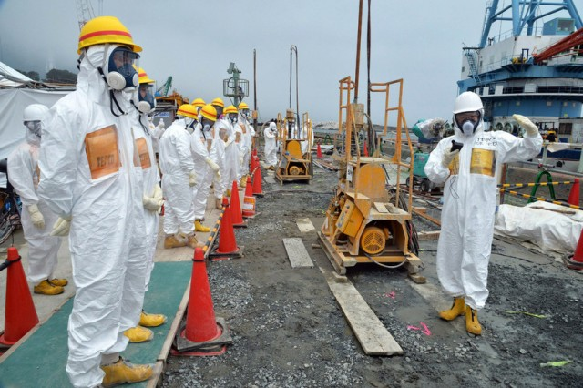 Japanese government officials and nuclear experts inspect work at the badly damaged Fukushima nuclear plant.  (AFP-Getty Images)