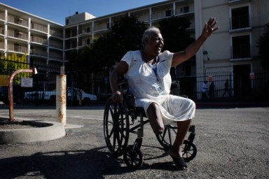 Rhonda Marshall, 58, waves to visitors outside the Hacienda public housing complex. She's been living on the high-rise's first floor for years and has watched the building deteriorate. She says sees cracks in the walls running from the sixth floor to the ground and smells mold in the hallways and stairwells. (Lacy Atkins/San Francisco Chronicle)