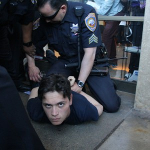 City College student Otto Pippenger is detained by SFPD officers outside an administration building. (Alex Emslie/KQED)