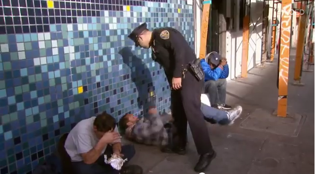 A San Francisco police officer rousts a man sleeping on a Tenderloin sidewalk. (KQED)