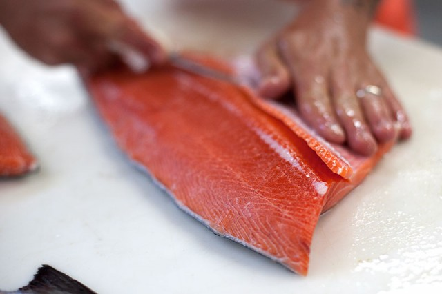 Kenny Belov, co-owner of TwoXSea, cuts a piece of salmon (Mark Andrew Boyer/KQED)
