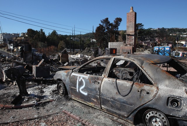 The shell of a car sits in the driveway of a burned home near the epicenter of the gas line explosion that devastated San Bruno. (Justin Sullivan/Getty Images)