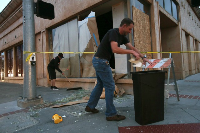 Workers clean up broken glass in front of a damaged building. (Justin Sullivan/Getty Images)