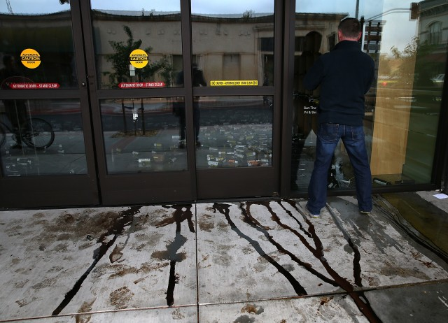 Vinegar flows out of the front door of a business damaged by the earthquake. (Justin Sullivan/Getty Images)
