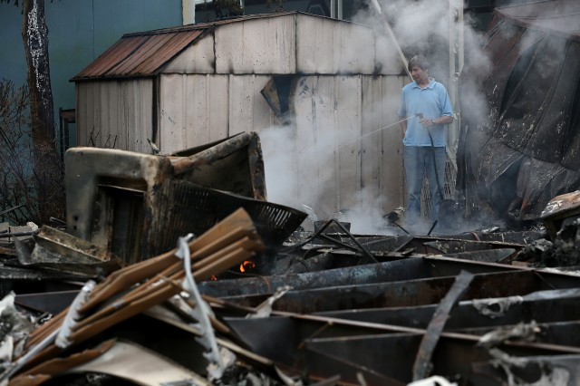 A man uses a garden hose cool hot spots from a fire at a mobile home park. (Justin Sullivan/Getty Images)
