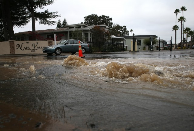 Water gushes from a water main break outside of a mobile home park. (Justin Sullivan/Getty Images)