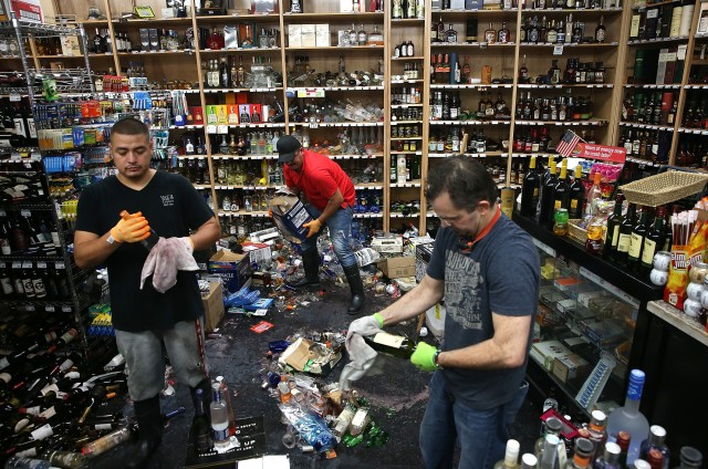 Workers clean up piles of bottles that were thrown from the shelves at Van's Liquors. (Justin Sullivan/Getty Images)