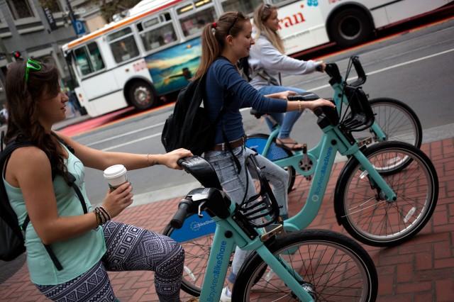 Shelby Larochelle from Canada, Hajnalka Domjan from Hungary, and Maria Camajova  from Slovakia rent bikes in San Francisco. (Mark Andrew Boyer/KQED)