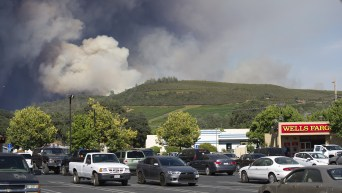 A column of smoke from the Rocky Fire rises above a shopping center in Clearlake on Sunday.