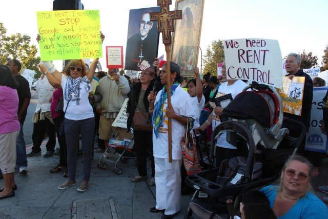 Marchers get ready to cross El Camino Real in Redwood City on October 1, 2015. They ask the City Council limits evictions and rent hikes.