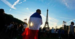 Suporter Prancis dengan benderanya di sela-sela nonton bersama di kawasan Fanzone Paris.