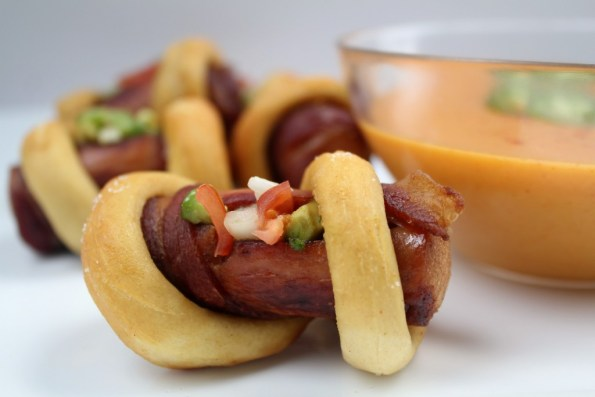 Hot dogs wrapped in bacon & pretzels with nacho cheese sauce