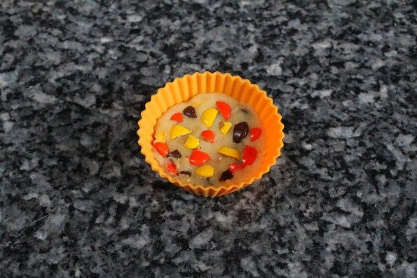 Press in one more layer of cookie dough, and then top it with chopped Reece's Pieces