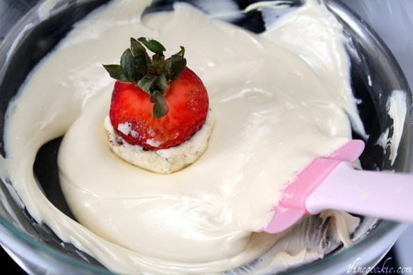 carefully scoop white chocolate onto strawberries