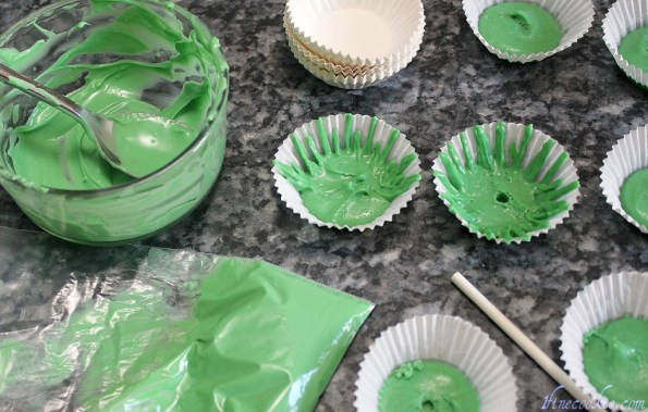 Pipe green chocolate out of a bag into cupcake liners
