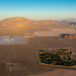 IVANPAH, CALIFORNIA, APRIL 05 2013: An aerial view of the Ivanpah Solar Power Facility at sunrise, with left to right Tower 1, 2 and 3, and the Primm Golf Course, bottom. Located in the Mojave Desert 40 miles southwest of Las Vegas, The Ivanpah Solar Power Facility is a solar thermal power project, currently under construction, with a planned capacity of 392 megawatts, enough to power approximately 140,000 houses. It will deploy 170,000 heliostat mirrors spread over 4,000 hectares, focusing solar energy on boilers located atop three solar power towers, generating steam to drive specially adapted steam turbines The project, developed by Bechtel, will cost $2.2 billion and be the largest solar farm in the world (photo Gilles Mingasson/Getty Images for Bechtel).