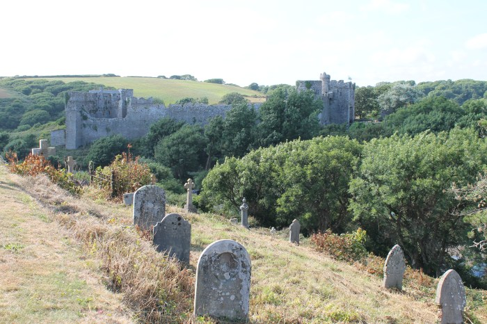 Very old weathered gravestones overlooking a medieval castle and rolling green hills