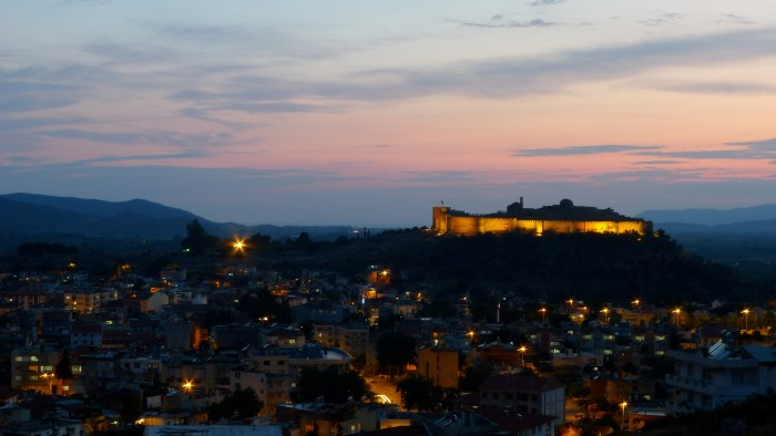 A castle on a hill overlooking a city at twilight