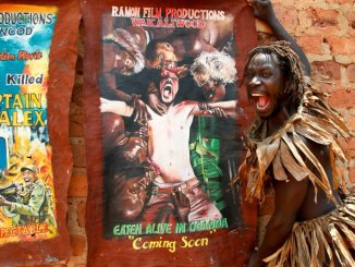 "In this photo taken Wednesday, Sept. 7, 2016, actor Francis Kagoro pulls a face for the camera while showing posters of previous movies, at the ""Wakaliwood"" studios in the Wakaliga slum of Kampala, Uganda. Deep in this Kampala slum at a tin-roofed collection of houses known as Wakaliwood, is the engine of Uganda's tiny film industry and the source of $200-budget movies and a glimmer of fame. (AP Photo/Stephen Wandera)"