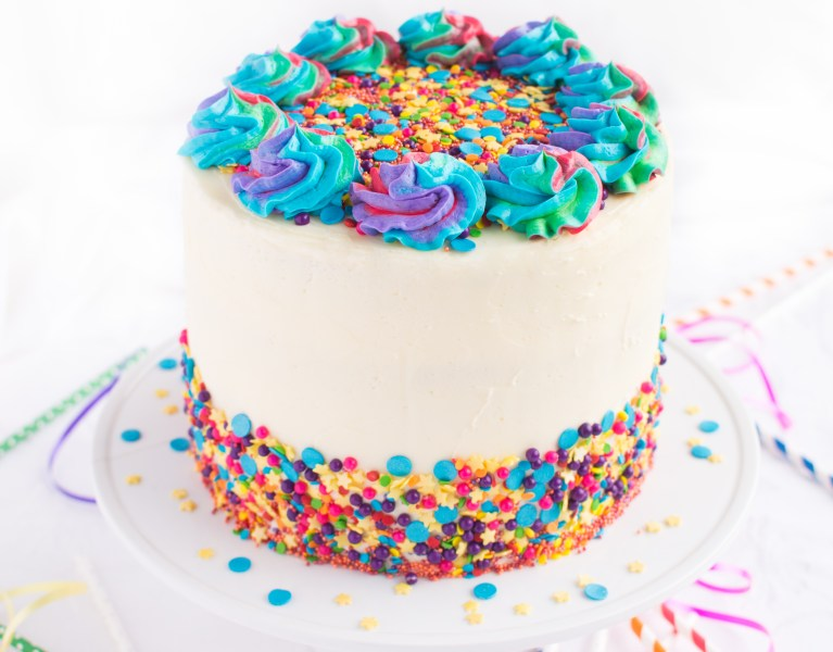 Soft and tender vanilla cake brimming with rainbow sprinkles, filled with rainbow chip cheesecake mousse and frosted in creamy vanilla buttercream! A childhood favorite made from scratch!