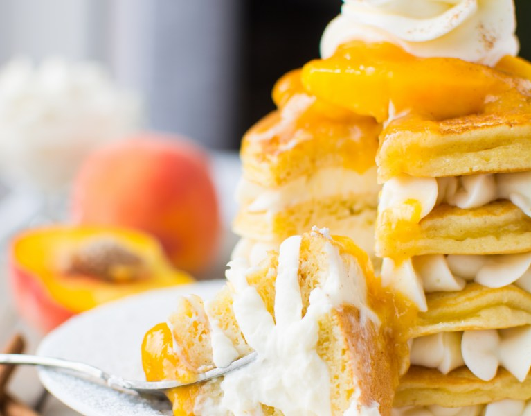 Fluffy pancakes layered with creamy white chocolate whipped filling and crowned with a bright and fruity peach topping!