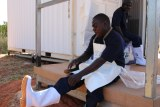 Indigenous fisherman Hans Lawrence puts on white gumboots to wear in the fish processing facility.