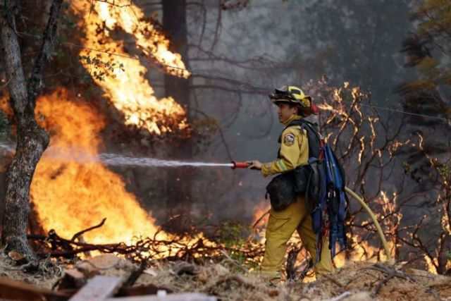 A firefighter hoses down flames as a wildfire advances
