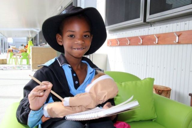 A student sits on a green lounge, holding a pencil, paper and a doll.