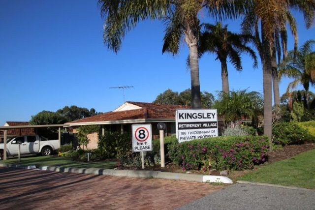 The exterior of Kingsley Retirement Village with shrubs and palm trees at the front of the property.