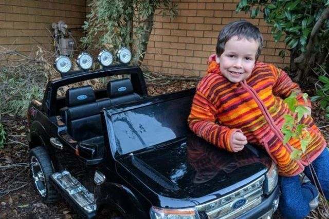 Phoenix Mapham leans on the bonnet of a small Ford Ranger.