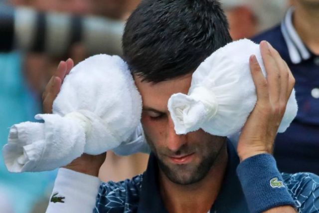 A tennis player sits with his eyes closed and an ice towel wrapped around his head