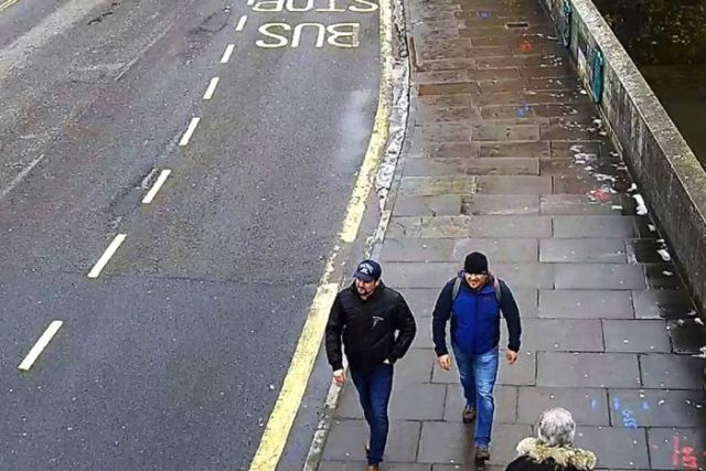 A image from a high vantage point shows two men walking down a deserted street.