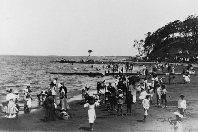 People on a beach in 1920.