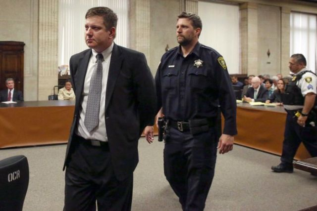 Jason Van Dyke is taken into custody by a court security guard