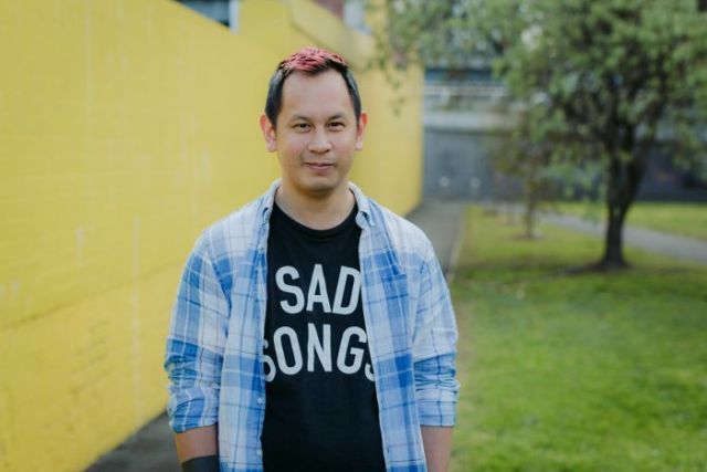 Colour photo of games designer Ken Wong standing outdoors in front in front of yellow wall.