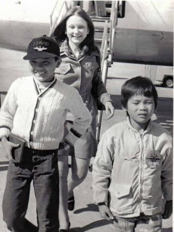 Two young boys disembark from a plane