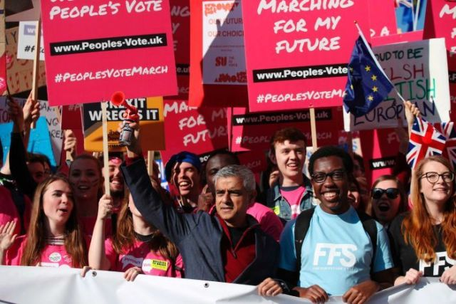 Mayor of London Sadiq Khan stands in a crowd of people holding red signs calling for a people's vote on Brexit.