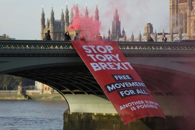 Protesters with red flares unfurl a banner saying 'Stop Tory Brexit' on Westminster Bridge in London.