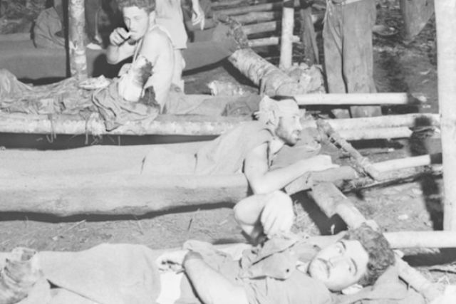 Wounded soldiers from the Battle for Gorari in Papua New Guinea in WWII lay on makeshift stretchers in November 1942.