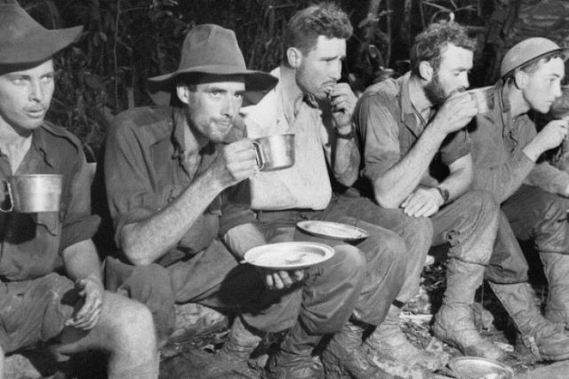 Wounded soldiers from the Battle for Gorari in Papua New Guinea eat and drink on their way back to Kokoda.
