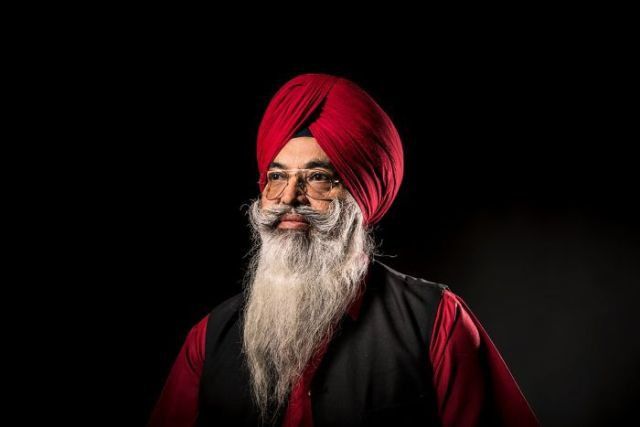 An elderly Sikh man, Darshan Singh Sidhu, wears a maroon-coloured turban and glasses.