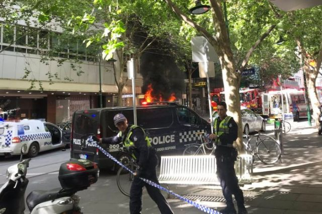 Victoria Police officers cordon off a road with flames in the background.