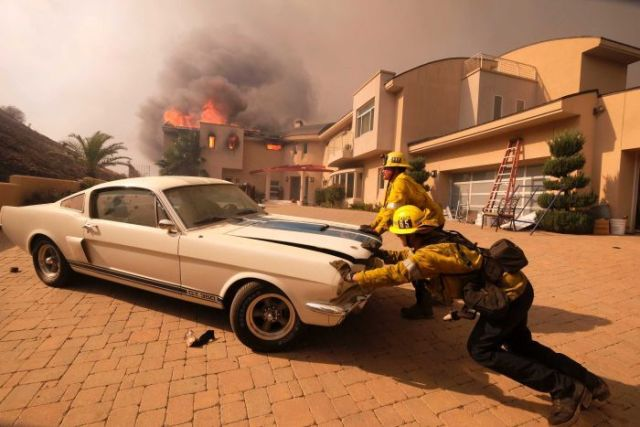 Firefighters push a vehicle from a garage as a wildfire fire burns a home